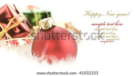 Christmas balls and gift boxes on white feather (with sample text) - stock photo