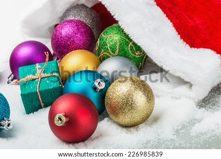 Christmas balls and gifts are scattered on the snow - stock photo