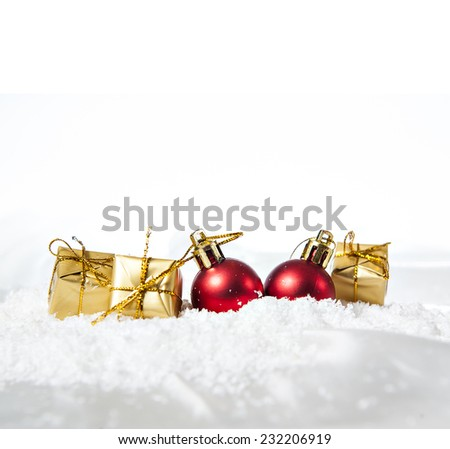Christmas balls and gifts in the snow. - stock photo