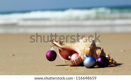Christmas balls and seashell on the beach - stock photo