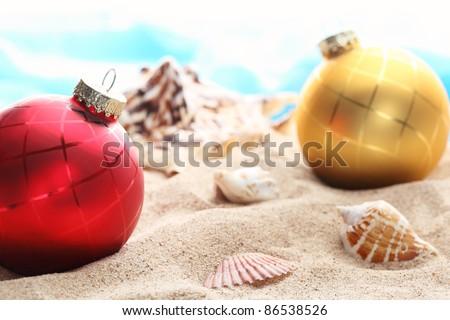 Christmas balls and seashells on the beach,Closeup. - stock photo