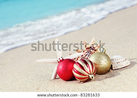 Christmas balls and seashells on the beach near the sea. - stock photo
