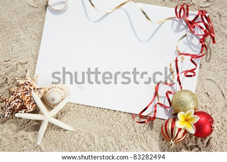 Christmas balls and seashells with blank card on the beach. - stock photo