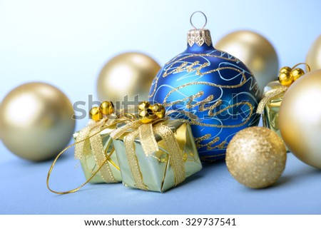Christmas balls blue and gold with gift box present on blue background new year