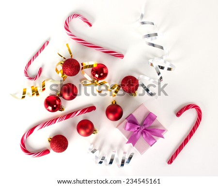 christmas balls, bright gold  bows,  lilac gift box and candy-canes on white surface, top view - stock photo