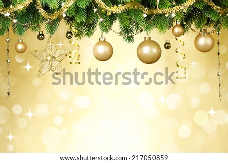 Christmas balls hanging on fir tree over festive background. - stock photo
