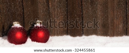 Christmas Balls in the snow in front of wooden background with copy space