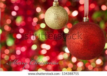 Christmas balls on illuminated background with 'Merry Christmas' - stock photo