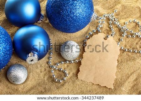Christmas balls with beads  on yellow sand - stock photo