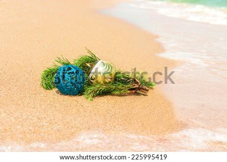 Christmas balls with fir twig on sand and sea - stock photo