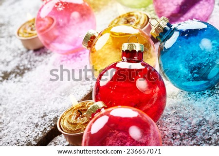 Christmas balls with golden candles and snowflakes on wooden background - stock photo