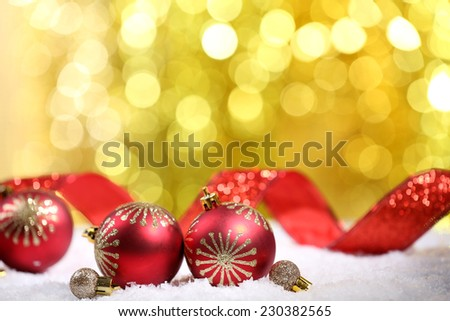 Christmas balls with red ribbon on snow on bright background