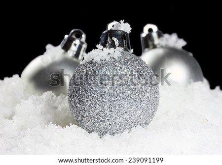 christmas balls with snow in tense light on black background  - stock photo