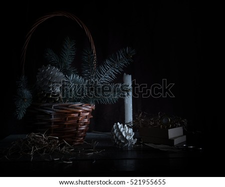 christmas. basket with fir branches and cones on a dark background.
