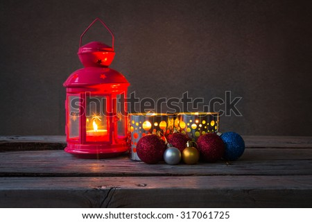 Christmas bauble and candle on wooden table over grunge background, selective focus, rustic style