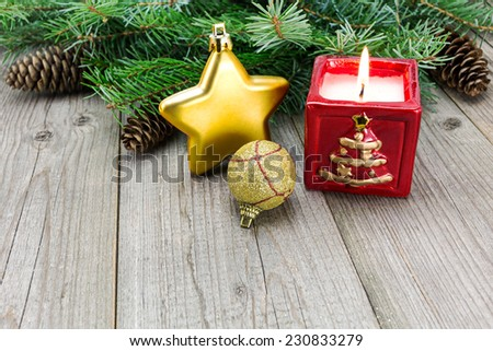Christmas bauble decoration with candle on weathered wooden plank - stock photo