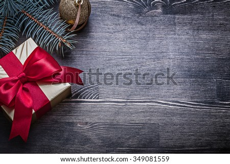 Christmas bauble pine branch gift box on wooden board. - stock photo