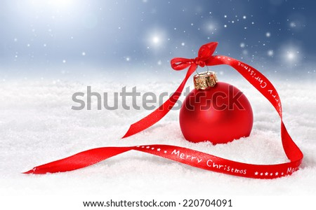 Christmas bauble with a red merry christmas ribbon in snow