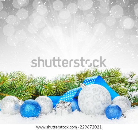Christmas baubles and blue ribbon with snow fir tree over bokeh background with copy space - stock photo