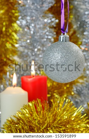 Christmas baubles and candles against a twinkling tinsel background - stock photo