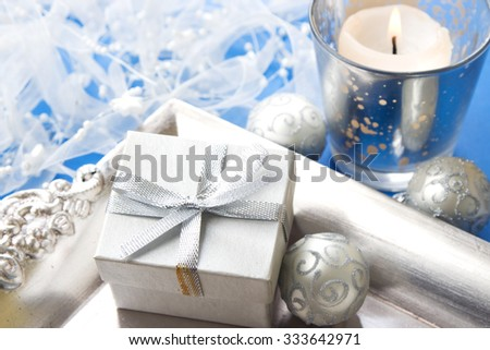 Christmas baubles and gift box, background with burning candle - stock photo