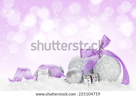 Christmas baubles and purple ribbon over snow bokeh background with copy space - stock photo
