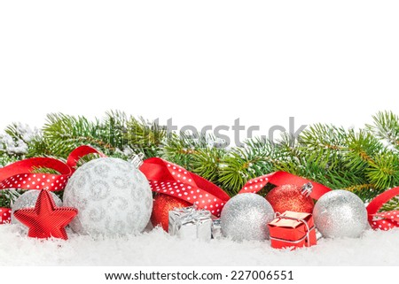 Christmas baubles and red ribbon with snow fir tree. Isolated on white background with copy space - stock photo