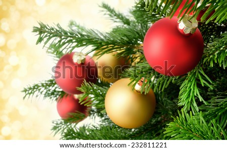 Christmas baubles hanging in a spiffy way on lush green branches of a fresh fir tree, with gold bokeh lights in the background - stock photo