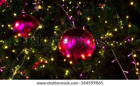 Christmas baubles hanging in a spiffy way on lush green branches of a fresh tree - stock photo