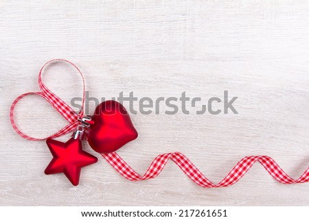 Christmas baubles heart and star with red and white checkered ribbon on light wood , copy space