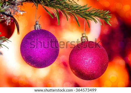 Christmas baubles in violet colors hanging from a branch - stock photo
