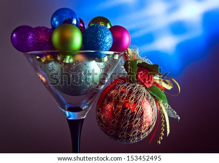 christmas baubles in wineglass on a dark background. - stock photo