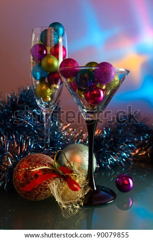 christmas baubles in wineglasses on a glass table. - stock photo