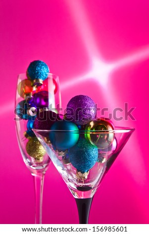 christmas baubles in wineglasses on a purple background. - stock photo