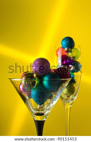 christmas baubles in wineglasses on a yellow background. - stock photo