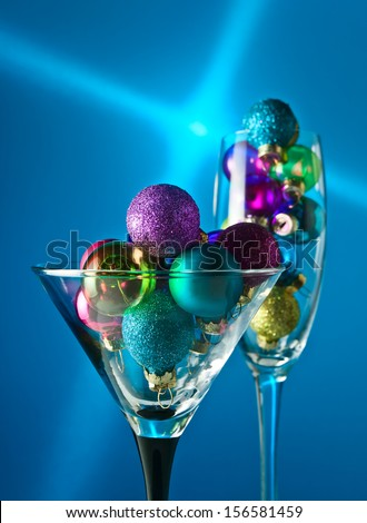 christmas baubles in wineglasses on blue background. - stock photo