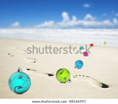 Christmas baubles on a beach with footprints - stock photo