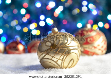 Christmas baubles on snow and lighting background