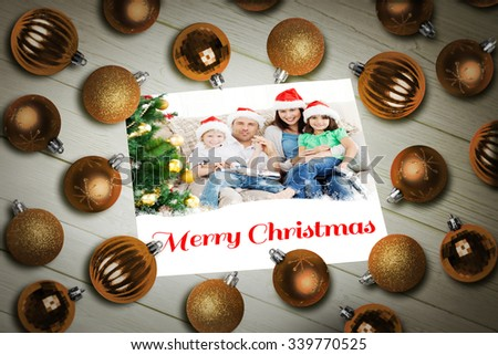 Christmas baubles on table against a happy family christmas card - stock photo