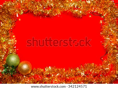 Christmas baubles with lights and tinsel frame on red background - stock photo