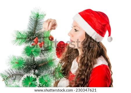 Christmas. Beautiful woman in santa costume decorating christmas tree. X-mas, winter, happiness concept  - stock photo