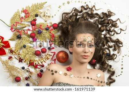 christmas beauty close-up portrait of sensual curly brunette girl with splendid eyes surrounded by colorful xmas decorations, red baubles, golden branch, ribbon and stars on her face.  - stock photo