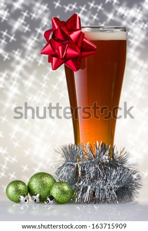 Christmas Beer with a Bow, garland, and Ornaments on a Sparkling Background - stock photo