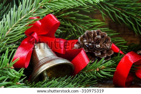 Christmas bell with a red ribbon, pine-needles and cones on old wooden background, selective focus - stock photo