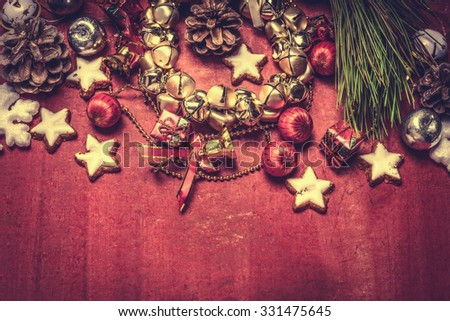 Christmas bell wreath and decorations on red wooden background, top view, border