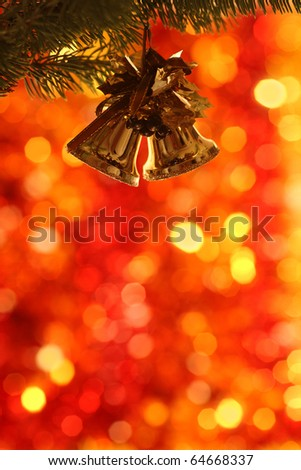 Christmas bells on branch of fir-tree against blurred background - stock photo