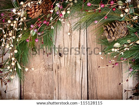 Christmas berries and pine branches on wooden background - stock photo