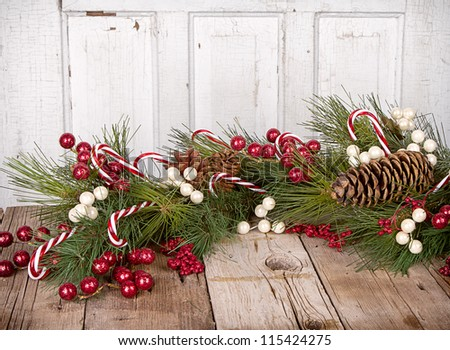 Christmas berries, Candy canes and pine branches on wooden background - stock photo