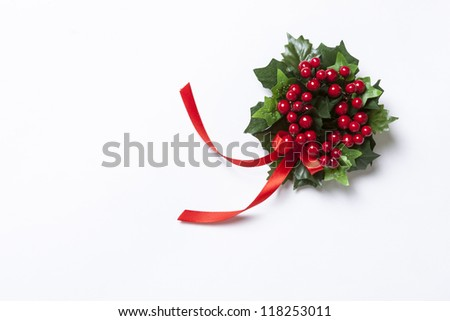 Christmas Berries garland with red ribbon and green leaves over white background. - stock photo