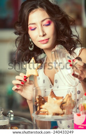 Christmas biscuit concept. Portrait of young brunette with arty make-up holding gingerbread posing with glass containers full of cookies in vintage cafe, restaurant. Retro style. Close up. Indoor shot - stock photo